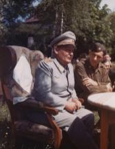 Hermann Göring on what appears to be a subsequent day after his surrendered, sitting down with Major Paul Kubala from U.S. forces.