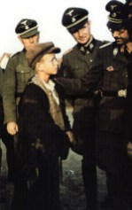 "Reichsführer-SS Heinrich Himmler (right) and an Ukrainian child destined for the Lebensborn Project, 1941. In the centre is Himmler's Chief of adjudant SS-Gruppenführer und Generalleutnant der Waffen-SS Karl Wolff, while at left is Himmler's driver and bodyguard, SS-Obersturmführer Josef ""Sepp"" Kiermaier."