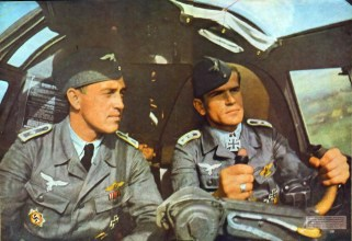 """Oberfeldwebel Johann-Peter Oekenpöhler (right) with his co-pilot. The original caption from SIGNAL magazine: """"wei Frontbewährte dt. Feldwebel probieren ein neues Modell aus. Bald sind sie wieder an der Front und noch besser für den Feind gerüstet"""" (Two front sergeant try a new model for approval. Soon they are back on the front and even better equipped for the enemy)."""
