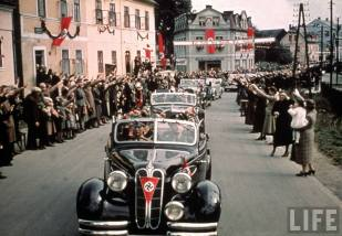 Nazi staff cars entering a Sudetenland village to receive an enthusiastic reception.