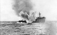 A U-boat shells a merchant ship which has remained afloat after being torpedoed.