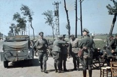 On the outskirts of Dunkirk, German officers confer by their vehicles at the roadside before moving into the town.