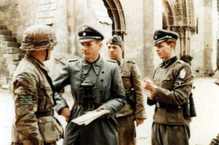 "At the building of l'Abbaye d'Ardenne (Ardenne Abbey), regimental command post of the SS-Panzergrenadier-Regiment 25 / 12.SS-Panzer-Division ""Hitlerjugend"" in Caen, Normandy, late June 1944. On the left wearing Italian Telo Mimetico M29 camo is the regimental commander SS-Obersturmbannführer Heinz Milius, who was to report the recent battle situation to SS-Sturmbannführer Hubert Meyer (Ia Erster Generalstabsoffizier of 12. SS-Panzer-Division ""Hitlerjugend"", Chief of staff). On the right wearing Demjanskschild is SS-Obersturmführer Bernhard-Georg Meitzel (Ib Quartiermeister of 12. SS-Panzer-Division ""Hitlerjugend"", Supply Officer in the Division staff), while the NCO behind Meyer is SS-Oberscharführer Herbert Reinecker (1914-2007), who served as an SS-Kriegsberichter."