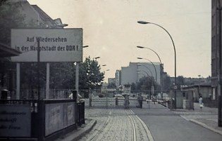 """A sign reading """"Come back to the capital of GDR""""."""
