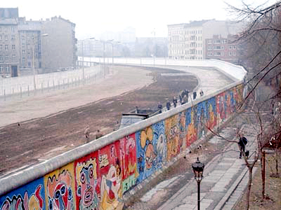"View from the West Berlin side of graffiti art on the wall in 1986. The wall's ""death strip"", on the east side of the wall, here follows the curve of the Luisenstadt Canal (filled in 1932)."