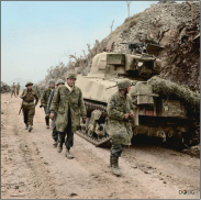Captured German parachute troops file past a Sherman tank of the New Zealand 4th Armoured Brigade at Cassino, 16 March 1944.