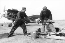 Service men cleaning the cannons of a Bf 109F, March 1942.