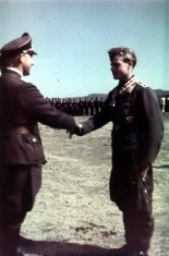 "Ritterkreuz (Knight's Cross) award ceremony for Luftwaffe fighter ace, Oberfeldwebel Rudolf Müller (Flugzeugführer in 6.Staffel / II.Gruppe / Jagdgeschwader 5 ""Eismeer""), that was held at Petsamo airfield (Finland) in 19 June 1942. Müller was awarded the Ritterkreuz after he scored his 46th air victory."