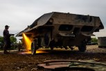 A worker cuts the body of a decommissioned armoured vehicle in the compound of the Koch Battle Tank Dismantling firm.