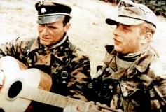 "During a break in the fighting, SS-Untersturmführer Franz-Josef ""Franzl"" Kneipp (Signal officer of III.Bataillon / SS-Panzergrenadier-Regiment 25 / 12.SS-Panzer-Division ""Hitlerjugend"") plays his guitar in the trenches with the battalion adjutant, SS-Untersturmführer Kurt Bergmann, and just out of sight to the left is Battalion Commander SS-Obersturmbannfuhrer Karl-Heinz Milius."