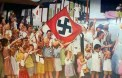 German civilians from Batavian Dutch internment camp celebrating the Japanese invasion of Java island (Dutch East Indies) in 1942. They are waving the Nazi and Japanese flags together.