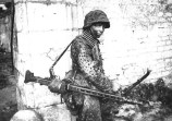 A German Waffen SS Hitlerjugend soldier involved in heavy fighting in and around the French town of Caen in mid-1944. He is carrying an MG 42 configured as a light support weapon with a folding bipod and detachable 50-round belt drum container.