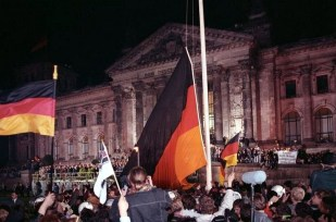 German people raising the German Flag in front of the Reichstag building, 1990.