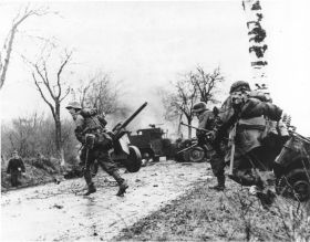 German troops advancing past abandoned American equipment.