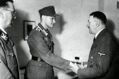 In the first days of August 1944, Adolf Hitler receives Wachtmeister Arthur Adam. Following the assassination attempt of 20 July 1944 he was the first to become suspicious of Oberst Claus Schenk Graf von Stauffenberg. It was he who noticed that the colonel left the conference early and had forgotten his briefcase and service cap in the outer office. After a vain attempt to report this to the two responsible intelligence officers, he turned directly to Reichsleiter Martin Bormann who took him to Hitler in order to state his suspicions. For his deeds, Wachtmeister Arthur Adam was promoted to Oberwachtmeister and received a small house near Berlin and 20,000 RM (Reichsmark).