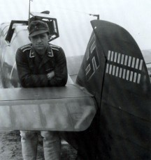 "This picture show one of the pilots who flew in the shadows of the aces. He is Unteroffizier Gerhard Proske of 1.Staffel / Jagdgeschwader 54 (JG 54) near the tail of his Messerschmitt Bf 109 G-2 ""Weiße 7"", Werknummer 10411. Note Gruppe and Geschwader emblem under the cockpit. Picture taken on 1 October 1942 on Krasnowardeisk airfield."