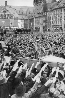 Adolf Hitler drives through the crowd in Eger, 3 October 1938.