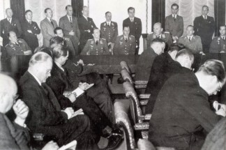"""Berlin, 20 December 1939 – a press conference organized by Dr. Otto Dietrich of Goebbels' Propaganda Ministry on the occasion of a great victory over British bombers achieved by German fighters over the Wilhelmshaven area on 18 December 1939. Seated at the table are pilots who fought in this battle. On the extreme right is Oberleutnant Wolfgang Falck of I.Gruppe / Zerstörergeschwader 76 (ZG 76); third from the right is Oberstleutnant Carl Schumacher, Gruppenkommandeur Jagdgeschwader 1 (JG 1); between Falck and Schumacher is Dr. Otto Dietrich in SS-Gruppenführer uniform; and third from the left is Oberleutnant Johannes Steinhoff of 10.(N)Staffel / III.Gruppe / Jagdgeschwader 26 (JG 26) """"Schlageter"""". Both Oberleutnants (Falck and Steinhoff) claimed two victories in the battle, while the commander of the whole formation (Schumacher) claimed one."""