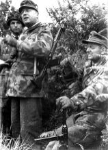 Dipl. Ing. Richard Schimpf in camouflage uniform and with a FG 42 shouldered as commander of the 3rd Paratrooper Division in Normandy , right is Knight Cross carrier Major of the Reserve Friedrich Alpers with a MP 40 , commander of the 1st Battalion of the Paratroopers Regiment 9th Schimpf's division was under the command of II Parachute Corps of Lieutenant-General Eugen Meindl.