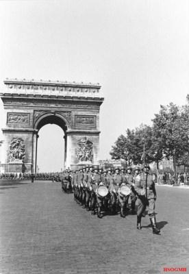 German soldiers march by the Arc de Triomphe on the Avenue des Champs-Élysées in Paris, June 1940.