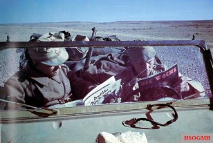 """German Afrikakorps soldiers reading """"Deutsche Illustrierte"""" and """"Die Woche"""" magazines in their staff car that parked in the barren North African desert, while a Kar98k rifle protruding in the back seat. """"Deutsche Illustrierte"""" was a large-format weekly magazine, while """"Die Woche"""" was a weekly issued family magazine. These magazines are packed with photos and home front activities. It also depicts news, art, culture etc."""