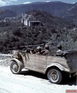 A German VW Typ 82 leichter geländegängiger Personenkraftwagen Kübelwagen in front of the backdrop of a mountain village in San Piero Patti, Messina, Sicily, Italy, with the castle-like structure of Convento dei Carmelitani, 1943.