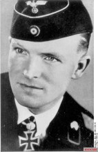 Helmut Hudel wears a knight's cross with oak leaves around his neck.