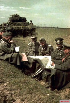 This picture was taken during Unternehmen Barbarossa, summer 1941. From right to left: Generaloberst Heinz Guderian (Oberbefehlshaber Panzergruppe 2), Generalleutnant Hans-Jürgen von Arnim (Kommandeur 17.Panzer-Division), General der Panzertruppe Joachim Lemelsen (Kommandierender General XXXXVII.Armeekorps), unknown officer, and Generalmajor Walther Nehring (Kommandeur 18.Panzer-Division). For the last ID (Nehring), it could be also Oberst Rudolf Bamler (Chef des Stabes XXXXVII.Armeekorps). In the background parked Panzerkampfwagen III.