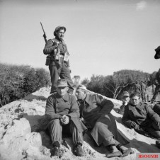 A British soldier guards a group of German prisoners at Anzio, 22 January 1944.