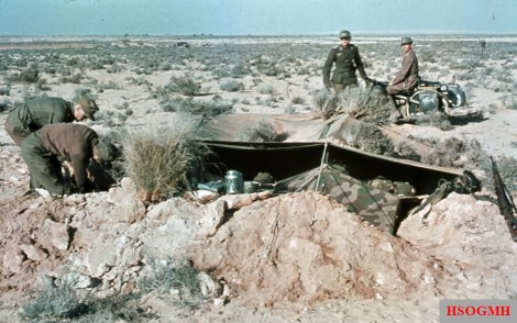Soldiers of the Deutsches Afrikakorps (DAK) making a small trench as their home in the desert. They used Zeltbahn as cover and camouflage from the air and distance. Photo taken by General Erwin Rommel during his Campaign in North Africa, 1941.