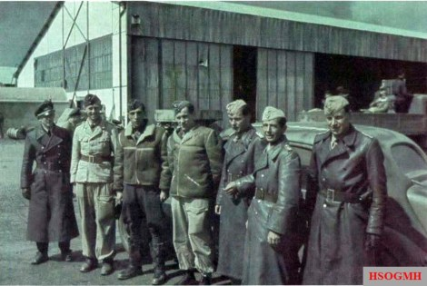 "A group of II.Gruppe / Jagdgeschwader 2 (JG 2) ""Richthofen"" personnel in Tunisia, early 1943. Third from the left is Oberleutnant Erich Rudorffer (temporary Gruppenkommandeur of II./JG 2), who ended the war as a Major with 224 victories and the recipient of Ritterkreuz des Eisernen Kreuzes mit Eichenlaub und Schwertern. To the right of Rudorffer is Oberleutnant Kurt Bühligen (Staffelkapitän 4./JG 2). One of the most successful German pilots in Tunisia, scoring 40 kills there. Bühligen ended the war as an Oberstleutnant with 112 victories and got the Ritterkreuz des Eisernen Kreuzes mit Eichenlaub. Following the hospitalisation of Hauptmann Adolf Dickfeld (136 victories, RK-EL) with injuries received in a landing accident, Oberleutnant Rudorffer assumed temporary command of II./JG 2."