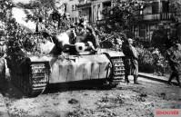 Soldiers ride a Sturmgeschütz III through the streets of Arnhem shortly after Market Garden.