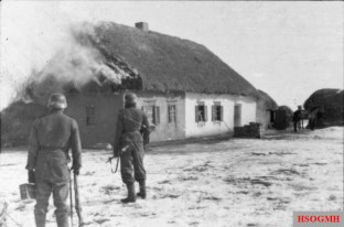 Waffen-SS men near a burning house, Kharkov, February 1943.