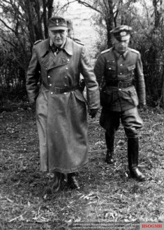 From an album of a Stabsoffizier of 281.Infanterie-Division. Here Generalleutnant Theodor Busse (Kommandierender General I. Armeekorps) walks together with Generalmajor Bruno Ortner (Kommandeur 281. Infanterie-Division). Busse is wearing the ledermantel (leather jacket). The picture was taken in 1944.