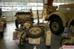 Located in a museum among other vehicles, a rear view of a desert camouflage BMW R75 motorcycle and sidecar. The sidecar has a spare wheel mounted horizontally on the rear.