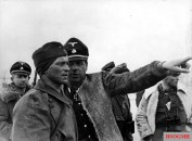 Fritz Witt (center) photographed in March 1943 as a commander of SS-Panzergrenadier Regiment 1 of the Leibstandarte Division. He holds the rank of SS-Standartenführer, but he has abandoned military etiquette and opted for comfort and warmth, commandeering a loose sheepskin jacket. Max Wünsche is right below Witt's hand.