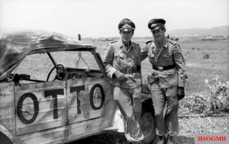 "Leutnant Reinert (left) and Feldwebel Maximilian Volke standing next to Hans-Joachim Marseille's ""Otto"" Kübelwagen, April 1943."