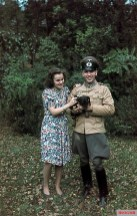 A noncommissioned officer of a German Army Artillery regiment - specializing in Transmissions - posing with a woman (probably his spouse) and puppy, near Tempelhof, Berlin, summer of 1943.