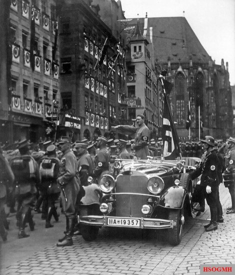 Adolf Hitler reviewing SA members in 1935. He is accompanied by the Blutfahne and its bearer SS-Sturmbannführer Jakob Grimminger.