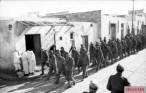 U.S. troops taken prisoner during the battle march through a Tunisian village.