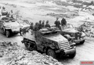 Rommel in Tunisia speaking with troops riding a captured American built M3 Half-track.