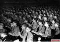 """Hitlerjugend demonstration under the banner of """"Die Ritterkreuzträger der Kriegsmarine Rede an die Hitlerjugend"""" (The Knight's Cross Recipients of the German Navy Speech to the Hitler Youth) at the Berlin Sportpalast, 16 June 1943. Young Hitlerjugend listen to the speech of Kapitänleutnant Reinhard Hardegen (Kommandant U-123)."""