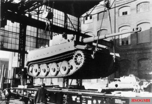 Tiger at the Henschel plant is loaded onto a special rail car. The outer road wheels have been removed and narrow tracks put in place to decrease vehicle width, allowing it to fit within the loading gauge of the German rail network.