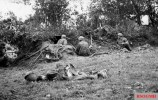 German paratroopers in the Battle of Carentan, in the foreground a fallen US American Airborne soldier of the 101st Airborne Division.