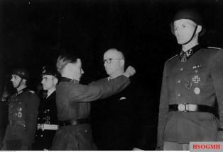 "Berlin, 20 May 1942: Ritterkreuzträger Gefreiter Hans Krohn of the 20.Infanterie-Division decorating the War Merit Cross without swords to Franz Hahne, headmaster in the company Rheinmetall -Altmärkische Kettenwerke (Alkett). At left is Captain Leo Drossel of the 24. Infantry Division and Lieutenant Commander Heinrich Liebe of U-38. At right is SS-Hauptsturmführer Heinrich ""Hein"" Springer of Leibstandarte SS Adolf Hitler."