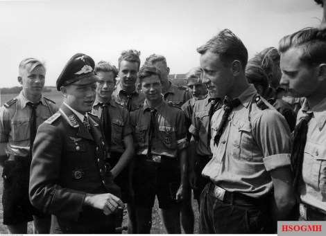 "Oberfeldwebel Wilhelm ""Willi"" Freuwörth from Jagdgeschwader 52 (JG 52) shares his experiences with the boys from the air section of the Hitlerjugend in Rossitten, East Prussia, 16 July 1944. In his sleeve is a cufftitle of ""Jagdgeschwader Schlageter"", the nickname of Jagdgeschwader 26 (JG 26), the first unit of Freuwörth."