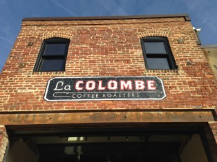 Faded auto repair signage under the new La Colombe sign.