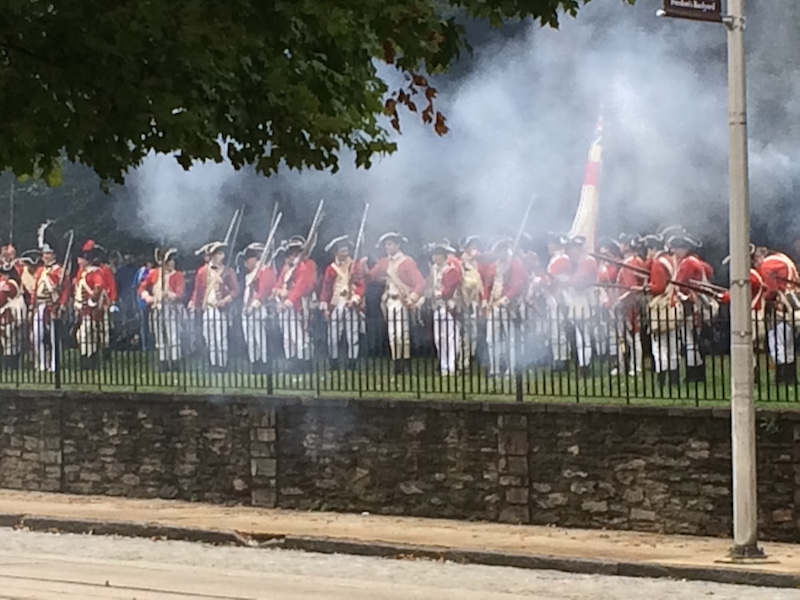 Actors playing the British troops, seen through a cloud of musket smoke