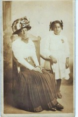Seated Woman Wearing Large Hat with Young Girl Standing at her Side