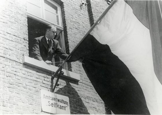 Landdrost Hubert Dassen plaatst Nederlandse vlag in Elten – Bron: Euregionaal Historisch Archief Sittard-Geleen